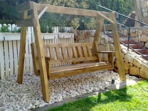 נדנדת עץ גושני בצבע עץ בחצר