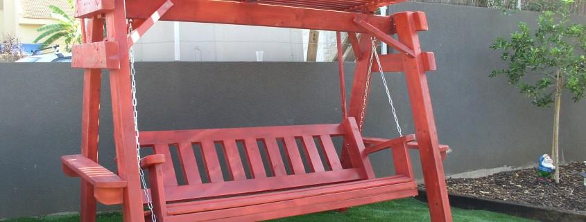 נדנדת עץ גושני בצבע אדום על הדשא