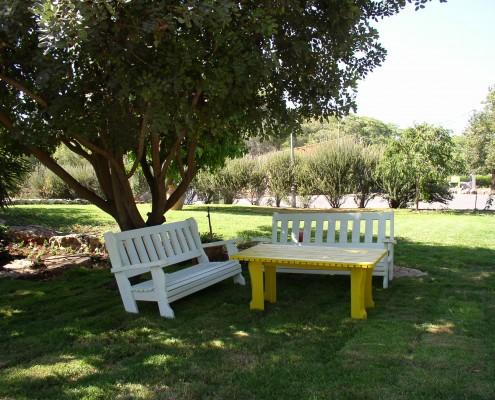 שני ספסלים לבנים ושולחן צהוב