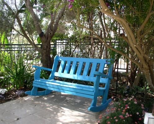 ספסל נדנדה כחול מתחת לעץ