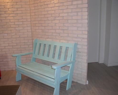 ספסל עץ מלא צמוד לקיר לבנים