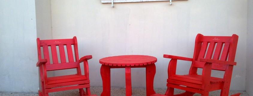 כסאות נדנדה בצבע אדום עם שולחן קפה